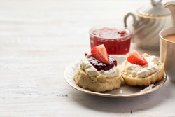 English tea with scones and clotted cream, jam, strawberries on the white table, copy space for text, selective focus