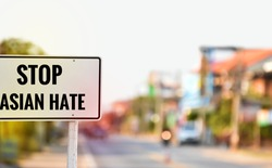 "English texts ""Stop Asian Hate"" on white traffic labels on pole, street blurred background, concept for calling the international drivers and passengers to stop hating and hurting Asian people."