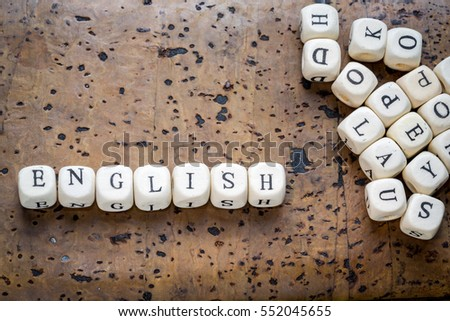 ENGLISH word written on wood block on a brown cork background with heap of blocks #552045655