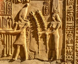 Engraved figure of the Egyptian gods, Horus and Hathor on the wall inside the Edfu temple in Egypt