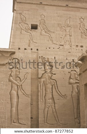 Engraved figures of Hathor, Horus, and Isis (partially visible) in Philae Temple near Aswan in Egypt
