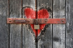 Engraved heart in the old wooden door with padlock