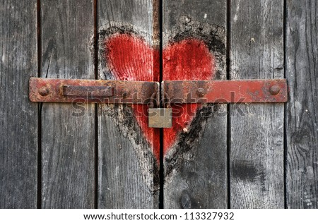 Engraved heart in the old wooden door with padlock - stock photo