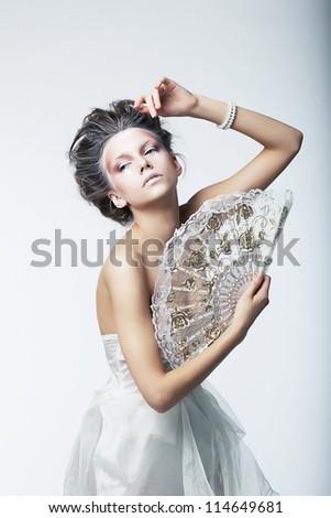 Enigma. Fantasy. Sophisticated retro fashion woman with white vintage fan.