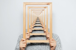 Enigmatic surrealistic optical illusion, young man holding frame on grey background.