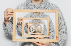 Enigmatic surrealistic optical illusion, young man holding frame on white background.