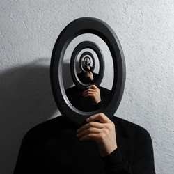 Enigmatic surrealistic optical illusion, young man holding round frame on textured grey background.