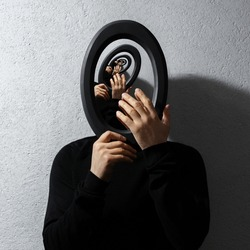 Enigmatic surrealistic optical illusion, young man holding round frame on textured grey background. Contemporary artwork collage concept.