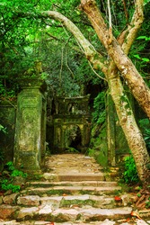 Enigmatic view of amazing old mossy stone gate and brick stairs leading to natural cave among green woods in the Marble Mountains (Ngu Hanh Son), Danang (Da Nang), Vietnam. Scenic forest in summer.