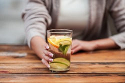 Enjoy freshness! Close-up of young woman stretching out glass with fresh lemonade while standing at the wooden desk