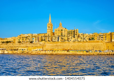 Enjoy iconic waterfront of Valletta from its Northern Harbor, watch medieval ramparts, historic residential quarters, bell tower of Anglican St Paul Pro-Cathedral and dome of Carmelite church, Malta