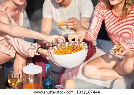 Enjoy it. Close up of bowl with snacks in hands of a young woman holding it while sharing with her friends