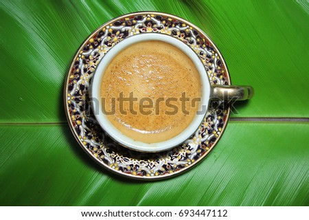 Shutterstock Enjoy morning coffee today with popular hot beverage menu,espresso coffee with golden fine-bubbled crema seen from above in antique ceramic cup on green leaf background in slow life day