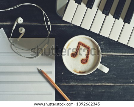Enjoy Music theme white cup of coffee with musical note symbol on frothy surface flat lay on black painted wood table with keyboard, pencil, blank staff notation sheet, earphones. (top view, close up)