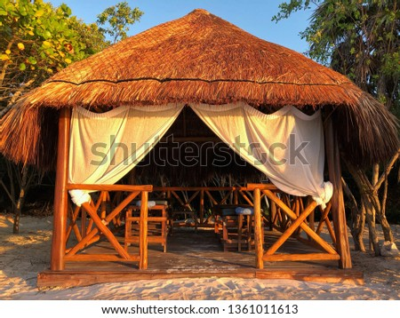 Enjoy pampering and relaxation in a peaceful natural setting, in an outdoor thatched roof massage hut on a white sand beach beside the ocean, with natural wood and white curtains, #1361011613