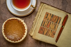 Enjoy Thanksgiving - letterpress typography in a retro, leather-bound journal with a pumpkin pie and a cup of tea, fall holiday greetings