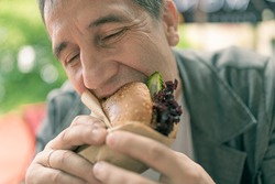 Enjoy your burger meal. The man eats a snack with salad and cucumber with pleasure and pleasure. Soft focus. Blurred background