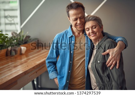 Enjoyable meeting. Waist up portrait of happy smiling aged woman and man tenderly embracing together while being in cafe