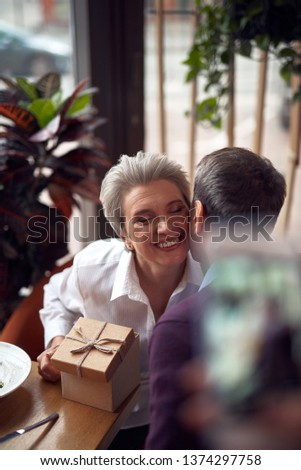 Enjoyable meetings. Close up top angle portrait of pleased elegant lady gratefully embracing male friend for present from him on meeting in cafe
