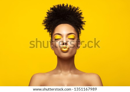 Enjoyed African American Fashion Model portrait . Satisfied Brunette young woman with afro hair style and closed eyes show kiss, creative yellow make up, lips and eyeshadows on colorful background.