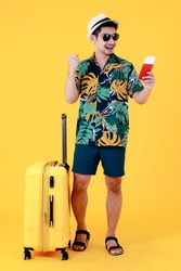 Enjoyed young Asian man in colorful Hawaiian shirt holds passport and make a winner gesture near suitcase. Full body studio portrait on yellow background. Happy summer vacation travel concept