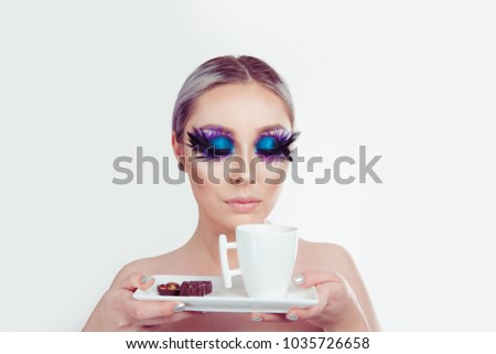 Enjoying aroma of a coffee cup. Beautiful woman with artistic purple blue eyes makeup feather on eyelashes eyes closed holding cup of tea and chocolates on white. Blue black swan and coffee concept #1035726658