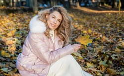 Enjoying autumn day. fallen leaves. nature beauty. beautiful blonde woman in puffer coat. autumn fashion and beauty. pretty girl has long curly blond hair. lady in fall padded jacket in forest
