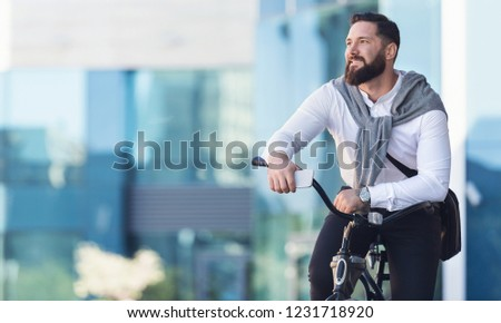 Enjoying beautiful cityview. Businessman leaning on bicycle, having break in riding, copy space