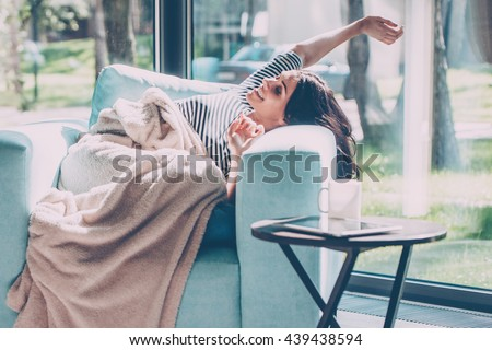 Enjoying beautiful morning. Beautiful young woman stretching out hands and smiling while lying in a big comfortable chair at home