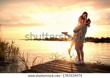 Enjoying By The River.Romantic smiling couple in love dating at sunset at river. Stock photo ©