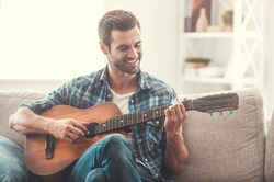 Enjoying carefree time at home. Happy young man playing the guitar while sitting on sofa at home