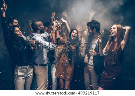 Enjoying carefree time together. Group of beautiful young people throwing colorful confetti and looking happy