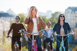 Enjoying carefree time with friends. Beautiful young smiling woman riding bicycle and looking away while her friends riding in the background