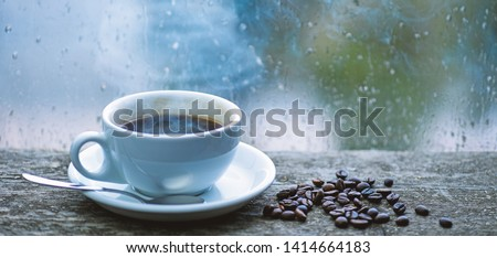 Enjoying coffee on rainy day. Coffee morning ritual. Fresh brewed coffee white mug and beans on windowsill. Wet glass window and cup of hot coffee. Autumn cloudy weather better with caffeine drink.