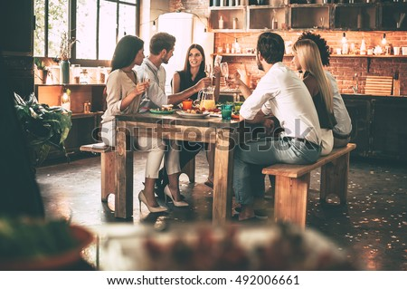 Enjoying dinner with friends. Group of cheerful young people enjoying dinner while sitting on the kitchen together #492006661