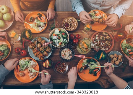 Enjoying dinner with friends. Top view of group of people having dinner together while sitting at the rustic wooden table