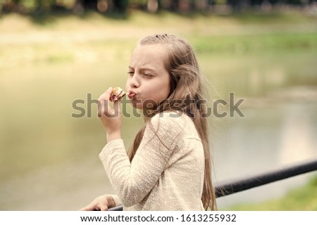 Enjoying every bite. Kid girl eat cookie. Health and dieting concept. Dieting counting calorie. Break her diet for sweets. Outdoors snack. Delicious cookie healthy snack. Sweet cookie pure enjoyment.
