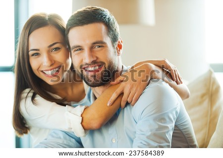 Enjoying every minute together. Beautiful young loving couple sitting together on the couch while woman embracing her boyfriend and smiling
