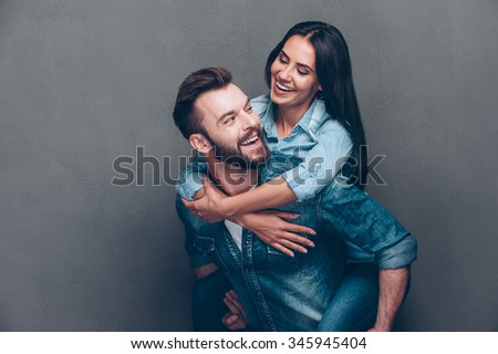 Enjoying every second together. Handsome young man piggybacking beautiful woman and smiling while standing against grey background