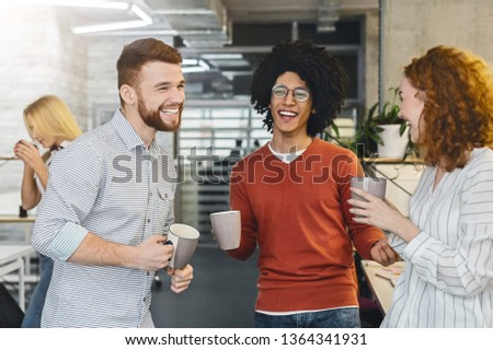 Enjoying free time. Group of millennial coworkers drinking coffee and talking in modern coworking space #1364341931