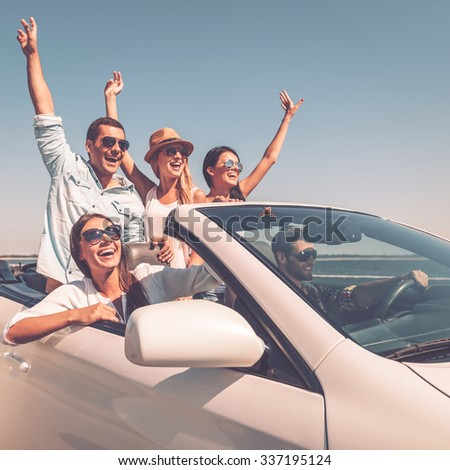 ENjoying friendly trip. Group of young happy people enjoying road trip in their white convertible and raising their arms up #337195124