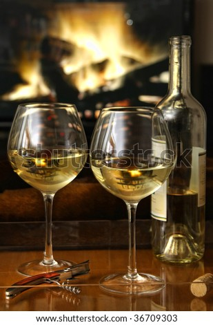 Enjoying glasses of white wine in front of a warm fire