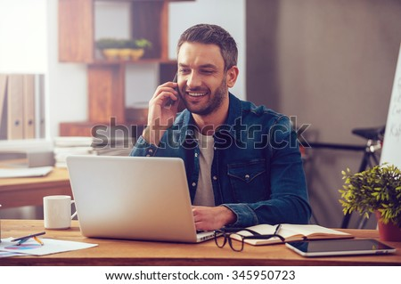 Enjoying good working day. Confident young man working on laptop and talking on the mobile phone while sitting at his working place in office