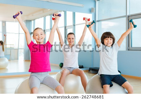 Enjoying healthy lifestyle. Cheerful mother and two children exercising with dumbbells in health club while sitting on the fitness balls