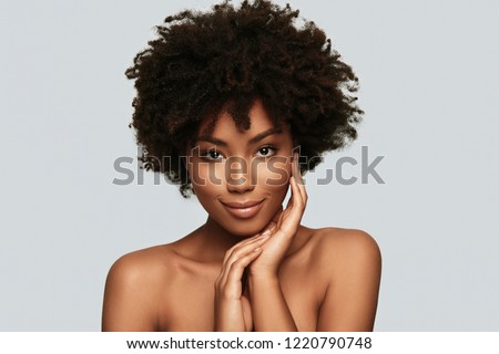 Enjoying her beauty. Attractive young African woman looking at camera and smiling while standing against grey background