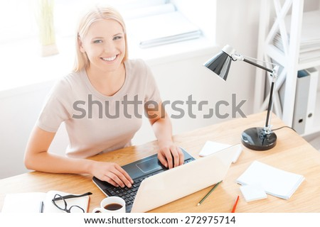 Enjoying her work. Top view of beautiful young woman looking at camera and smiling while sitting at her working place in office