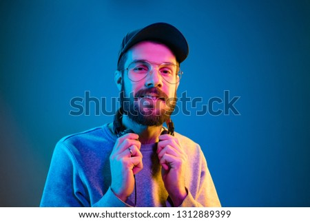 Enjoying his favorite music. Happy young stylish man in sunglasses with headphones smiling while standing against blue neon background #1312889399