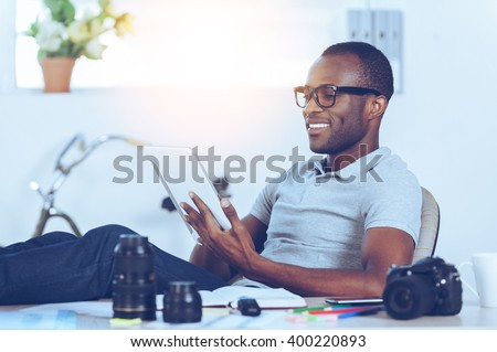 Enjoying his working day. Handsome young African man in casual wear sitting at his working place and working on digital tablet