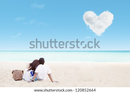 Enjoying honeymoon at white sand beach with love cloud - stock photo