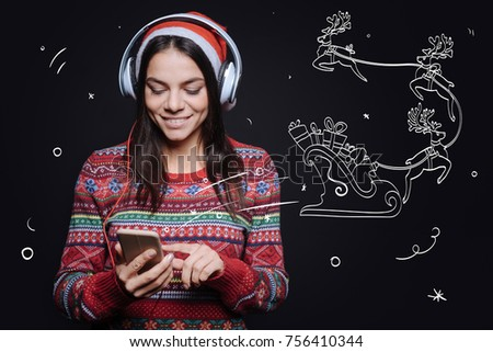 Enjoying jingle bells song. Cheerful amused young woman standing against imaginary drawing on the black wall and expressing happiness while listening to the Christmas songs #756410344